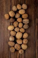 Top view of whole walnuts scattered on wooden background