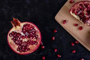 Top view of cut pomegranate on a blackboard on a black background