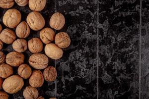 Top view of whole walnuts scattered on black wooden background with copy space
