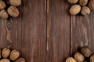 Top view of whole walnuts scattered on wooden background with copy space