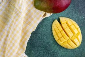 Top view of sliced mango with a yellow kitchen towel on a green background