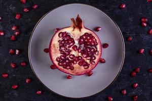 Top view of cut pomegranate on a white plate on a black background