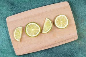 Vista superior de rodajas de limón en el tablero.