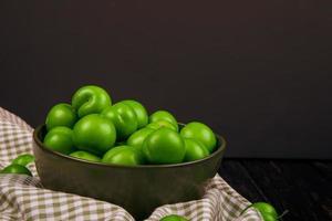 Vista lateral de ciruelas ácidas verdes en un recipiente sobre tela escocesa en fondo oscuro foto