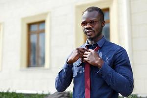 Handsome man fixes his tie