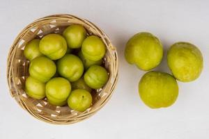 Top view of plums in basket and green pluots on white background
