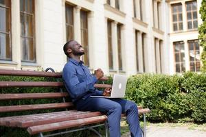 Man celebrating outside with laptop