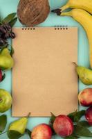 Vista superior del patrón de fruta alrededor del bloc de notas sobre fondo azul.