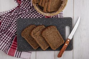 Top view of rye bread slices with knife photo