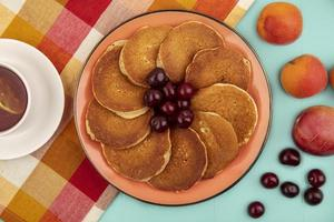 Top view of pancakes with cherries