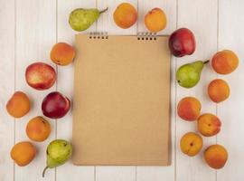 Vista superior del patrón de frutas alrededor del bloc de notas