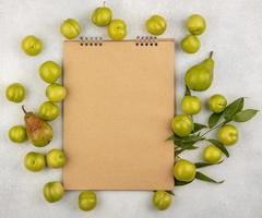 Top view of fruit around note pad on white background with copy space
