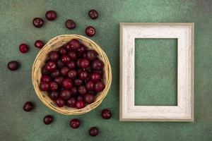 Top view of red cherries isolated on a green background with frame copy space