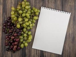 Top view of grapes and note pad on wooden background with copy space