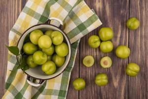 Top view of green plums in bowl on plaid cloth and on wooden background
