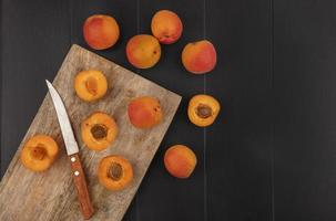 Top view of apricots with knife on cutting board
