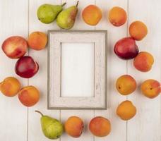 Vista superior de la fruta alrededor del bastidor sobre fondo de madera con espacio de copia foto