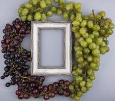 Top view of grapes around frame on gray background with copy space