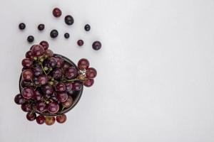 Top view of red grapes in bowl and on white background with copy space