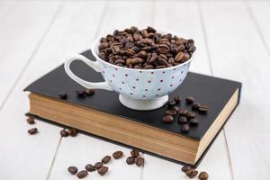 Vista superior de los granos de café tostados en una taza de lunares foto