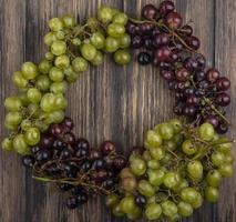Top view of grapes set in round shape on wooden background