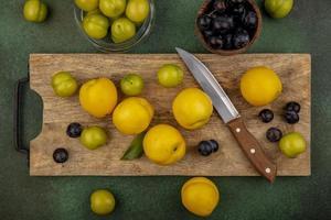 vista superior de duraznos amarillos frescos y ciruelas cereza verde foto