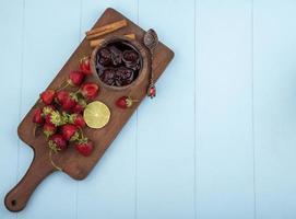 Vista superior de fresas frescas y mermelada en una tabla de cocina de madera
