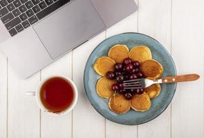Top view of pancakes with cherries with cup of tea