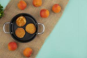 Top view of pancakes in pan and apricots on sackcloth on blue background with copy space photo