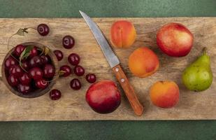 Top view of fruits on cutting board on green background