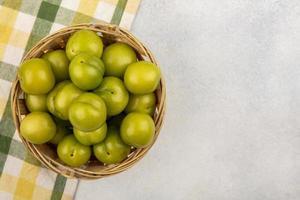 Vista superior de ciruelas verdes en canasta foto