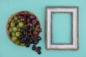 Vista superior de las uvas y un marco de madera sobre fondo azul.