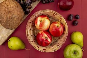 Top view of juicy peaches in a basket with pears on a red background