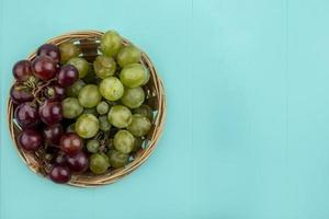 Top view of grapes in a basket on blue background with copy space