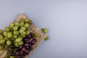 Top view of grapes on cutting board on gray background with copy space