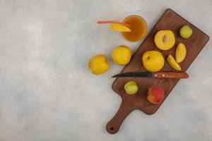 Vista superior de duraznos amarillos frescos sobre una tabla de cocina de madera foto