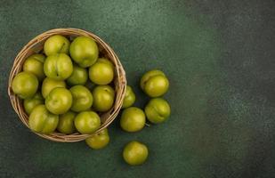 Vista superior de ciruelas verdes en una canasta foto