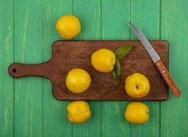 Top view of fresh yellow peaches on a wooden kitchen board