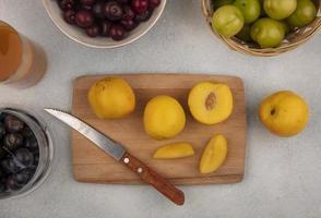 Vista superior de duraznos amarillos frescos sobre una tabla de cocina de madera