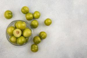 Vista superior de ciruelas verdes en jar y sobre fondo blanco con espacio de copia foto