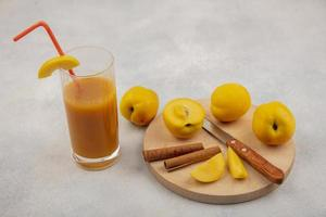 Top view of fresh yellow peaches and juice on a white background