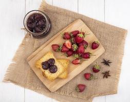 Vista superior de fresas frescas sobre una tabla de cocina de madera foto