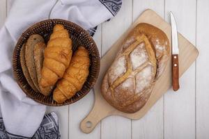 Assorted bread on cutting board on wooden background