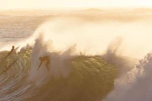 People riding a wave at golden hour