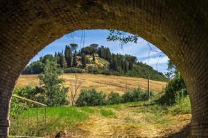 Tuscany, Italy, 2020 - View of a house on a hill through a tunnel