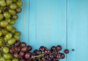 Top view of grapes on blue background with copy space