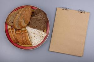 Top view of sliced bread with notepad on gray background with copy space