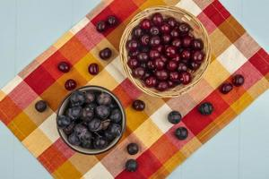 Top view of fresh red cherries and dark purple sloes photo