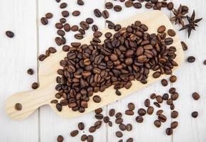 Vista superior de los granos de café tostados frescos aislado sobre un fondo de madera blanca foto