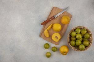Vista superior de duraznos amarillos frescos y ciruelas cereza foto